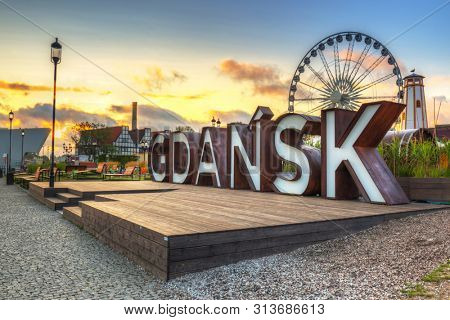 Gdansk, Poland - July 25, 2019: Beautiful architecture of Gdansk with an outdoor sign at sunrise, Poland