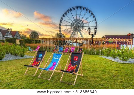 Gdansk, Poland - July 25, 2019: Relax zone at the park of Gdansk with ferris wheel at sunrise, Poland