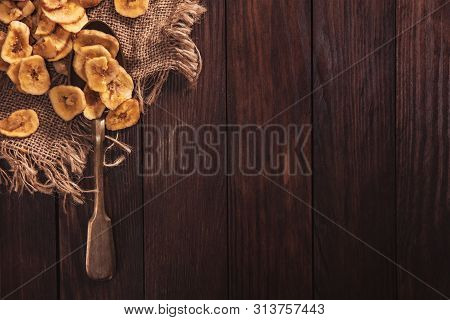 Dried Bananas Stacked On A Fabric And Spoon Over Old Brown Table. Composition In The Old Style With