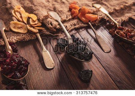 Dried Fruits Arranged On A Spoon, Fabric And An Old Table. Composition In The Old Style