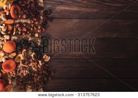 Mix Of Dried Fruit And Nuts Arranged On Linen Fabric And An Old Table. Composition In The Old Style