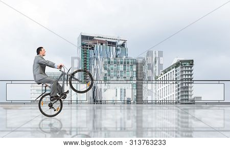 Man Wearing Business Suit Riding Bicycle On Penthouse Balcony. Handsome Cyclist Popped Wheelie On Ba