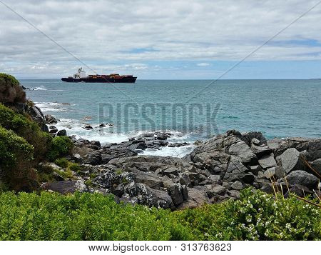 A Container Ship Is Leaving The Harbor Of Bluff, New Zealand