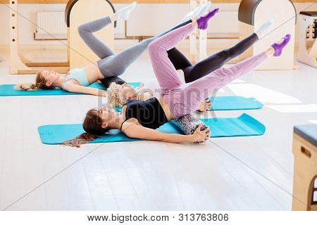 Female Instructor With Young Female And Senior Woman Together Using A Foam Roller For A Myofascial R