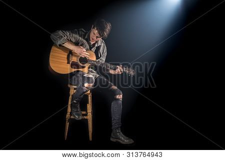Musician Playing Acoustic Guitar, Sitting On High Chair, Black Background With Beautiful Soft Light