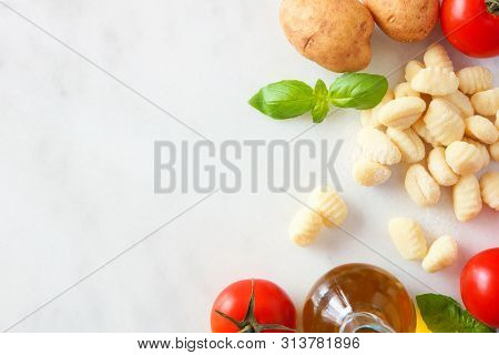Gnocchi Meal Ingredients Including Fresh Gnocchi, Tomatoes, Olive Oil, Potatoes And Basil. Top View,