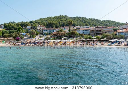 Photo Of The Beach With Umbrellas And Tourists Stock Photo