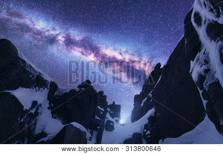 Milky Way And Snowy Mountains. Space. Beautiful Nature. Snow Covered Rocks And Starry Sky At Night.