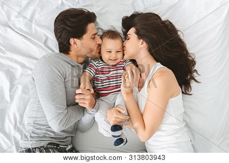 Enjoying Parenthood. Happy Caucasian Couple Kissing Sweet Cheeks Of Their Adorable Baby Son, Lying T