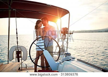 young man and woman sailing on the luxury boat together and enjoy at sunset on vacation