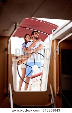 Happy man enjoying a summer day on a boat with her girlfriend
