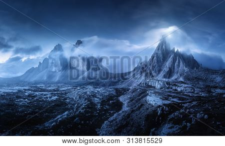 Mountains In Fog At Beautiful Night. Dreamy Landscape With Mountain Peaks, Stones, Grass, Blue Sky W