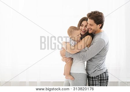 Family Tenderness. Loving Parents Cuddling With Little Baby Son At Window, Free Space