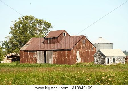 An Old Abandoned Farm Building With Ribbed Metal Siding. Probably Used For Storage.