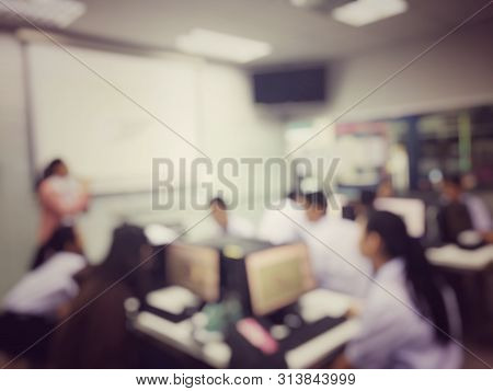 Blurred Image Of Group Of Students Are Learning And Sitting At Desk Using Computer Lap Together In C
