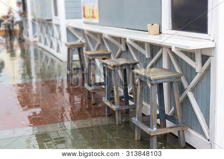 Wooden Furniture On A Wooden Deck On The Sidewalk Near Cafe And Restaurant With Nobody Around During