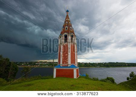 The Ancient Bell Tower Of The Kazan Church Against The Backdrop Of A Stormy Sky. Tutaev (romanov-bor