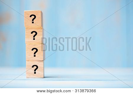 Questions Mark ( ? ) Word With Wooden Cube Block On Blue Table Background. Faq( Frequency Asked Ques