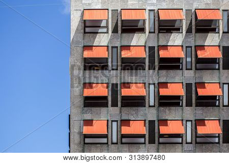 Many Red Awnings Over Windows On A Office Building.