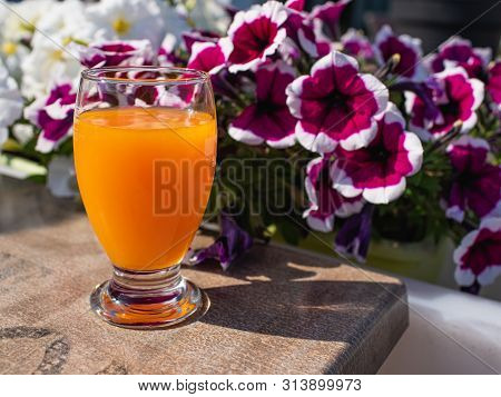 Full Glas Of Orange Juice On The Table, Outdoor, Sunny Morning