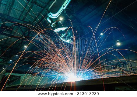 Welding Sparks  From Robot  In Manufacturing With Blur Focus, Used Is Background
