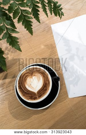 Coffee Cup And A Part Of Book On Wood Table With Ornament Fern Leaf.