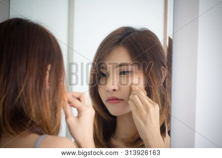 Portrait Beautiful Asian Girl Applying Powder Puff Foundationat Mirror In Bedroom. Young Woman Makeu