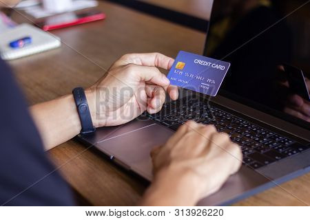 Business Man Hand Holding Credit Card Typing Laptop Computer, Payment Shopping Online. Close Up Man