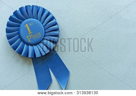Champion Or Winners 1st Place Blue Rosette With Gold Text On A Light Blue Background With Copy Space