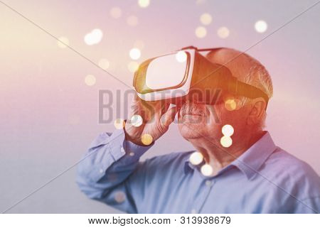 Elderly Man In Wonderment At A Virtual Reality Experience Wearing A Headset With A Glowing Bokeh Of