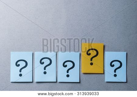 Four Question Marks On Blue And One On Yellow Arranged In A Line On A Grey Background With Copy Spac