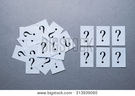 Still Life Of Printed Question Marks On White Paper With Six Arranged Neatly In Two Rows Alongside A