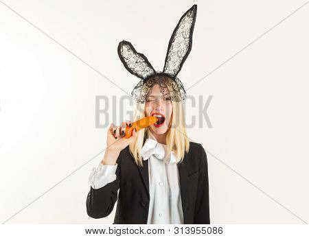 Happy Easter. Sexy Easter Bunny Eating Carrot. Sensual Woman Wearing Black Lace Easter Rabbit Ears.