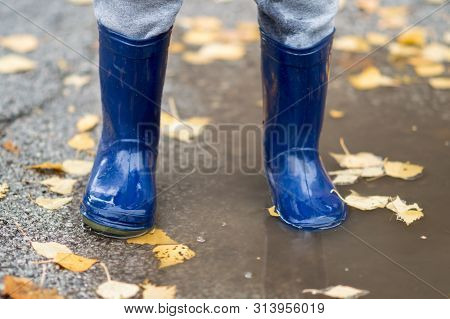 Feet Of Child In Blue Rubber Boots Jumping Over A Puddle After The Rain. Close Up Of Child Wellies I