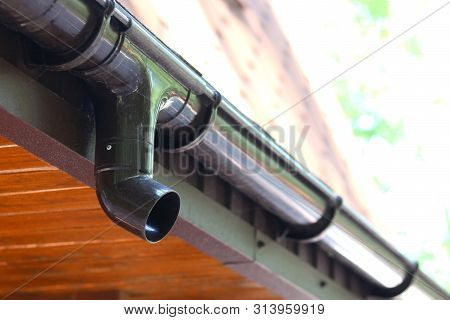 Modern Roof Of House With Plastic Rain Gutter On Beautiful Natural Background With Green Vegetation