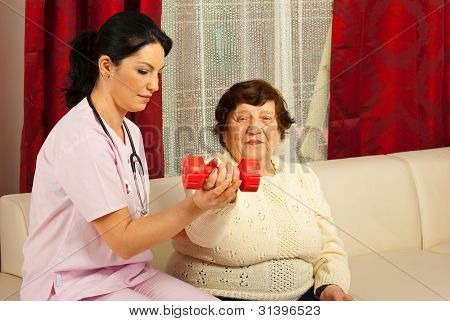 Therapist Helping Senior To Do Exercises