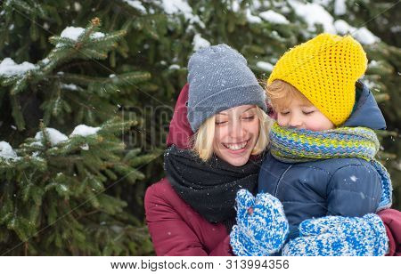Mom And Cute Child Warm Hat Scarf. Winter Fashion Concept. Happy Girl Playing With Kid Winter Day. E