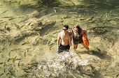 Couple of tourists on the transparent water of a river of Bonito MS, Brazil surrounded by a shoal of Piraputanga fishes. Brazilian ecotourism. poster