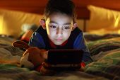kid in bed wih videogame console on night poster