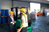 Front view of Caucasian female manager and male supervisor interacting with each other in warehouse. This is a freight transportation and distribution warehouse. Industrial and industrial workers poster