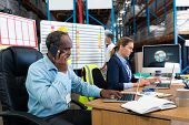 Side view of mature African-american male supervisor using laptop while talking on mobile phone at desk in warehouse. This is a freight transportation and distribution warehouse. Industrial and poster