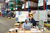 High angle view of mature Caucasian female manager and African-american male supervisor discussing over laptop at desk in warehouse. This is a freight transportation and distribution warehouse. poster