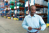 Front view of mature African-american male supervisor with headset using digital tablet in warehouse. This is a freight transportation and distribution warehouse. Industrial and industrial workers poster