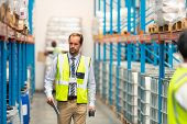 Front view of handsome mature Caucasian male supervisor walking in warehouse. This is a freight transportation and distribution warehouse. Industrial and industrial workers concept poster