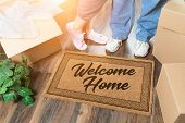 Man and Woman Unpacking Near Welcome Home Welcome Mat, Moving Boxes and Plant. poster