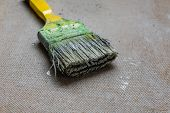 Dirty green paintbrush on chipboard. House renovation poster