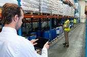 Rear view of mature Caucasian male supervisor working on digital tablet in warehouse. African-american colleagues working in front of him. This is a freight transportation and distribution warehouse. poster