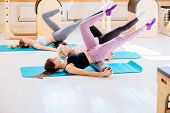 Female instructor with young female and senior woman together using a foam roller for a myofascial release massage at pilates studio. Healthy lifestyle rehabilitation small business concept. poster
