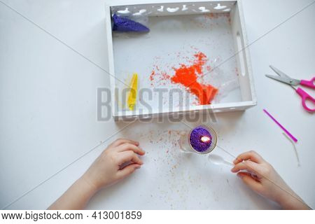 A Girl Makes A Candle From Small Paraffin Granules. Kids Pens Are Lying On A White Table Granules. P