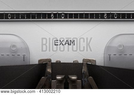 Typing text EXAM on vintage manual typewriter. Close up of writes word on white paper. Shot in macro.
